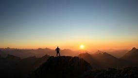 Mens die top bereiken die van vrijheid genieten en naar bergenzonsondergang kijken stock afbeelding