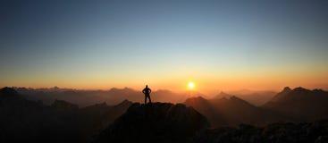 Mens die top bereiken die van vrijheid genieten en naar bergenzonsondergang kijken royalty-vrije stock afbeeldingen