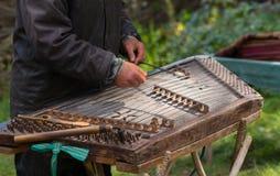 Mens die traditioneel gehamerd hakkebord spelen royalty-vrije stock foto's
