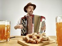Mens die in traditionele Beierse kleren harmonika spelen oktoberfest royalty-vrije stock afbeeldingen
