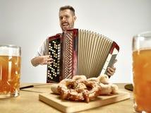 Mens die in traditionele Beierse kleren harmonika spelen oktoberfest stock foto's