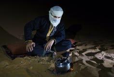 Mens die in traditionele Tuareg-uitrusting thee in een woestijn maken Stock Afbeeldingen