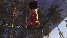 Mens die trucs die in lucht maken op trampoline op palmen en hemelachtergrond springen stock videobeelden