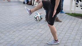 Mens die trucs met voetbal in de straat doen stock video