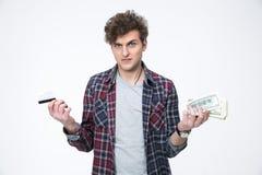 Mens die tussen bankwezenkaart of contant geld kiezen Stock Foto's