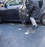 Mens die in of uit de achterbank van een 4 deurauto gaan binnen stappen stock foto