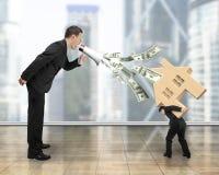 Mens die uit dollarrekeningen bespuiten die bij een ander dragend huis schreeuwen Royalty-vrije Stock Foto's