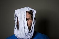 Mens die uit door het gat in het ondergoed op zijn hoofd gluren stock foto