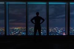 Mens die uit grote vensters hoog boven een uitspreidende stad kijken royalty-vrije stock foto