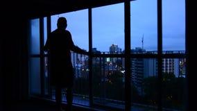 Mens die uit venster met mening van de stadshorizon van Auckland schemer bekijken stock video