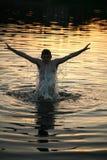 Mens die uit water springt stock foto's