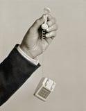 Mens die uiterst kleine stuk speelgoed telefoon houden Stock Foto's