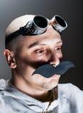 Mens die valse snor en beschermende brillen draagt Stock Afbeeldingen