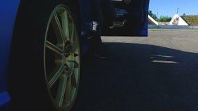 Mens die van blauwe auto weggaan en deur, automobiele demonstratie sluiten stock videobeelden