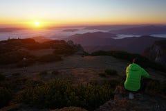 Mens die van de zonsopgang op de berg genieten Stock Foto's