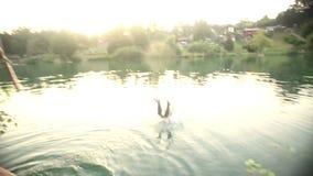 Mens die van een boom in rivier bij zonsondergang springen stock footage
