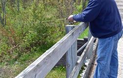 Mens die van een brug vissen Stock Afbeeldingen