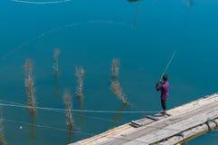 Mens die van een pijler vissen Royalty-vrije Stock Foto