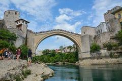 Mens die van een zeer hoge oude brug in Mostar springen Royalty-vrije Stock Foto's
