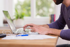 Mens die van huis aan een laptop computer werken Stock Afbeeldingen