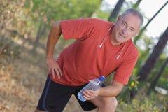 Mens die van oefening pauzeren om water te drinken royalty-vrije stock afbeelding