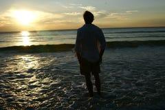 Mens die van zonsondergang geniet Stock Foto's