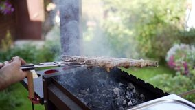 Mens die varkensvleesvlees op koperslager roosteren, die stukken wegknippen stock footage