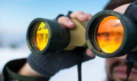 Mens die verrekijkers buiten op een de winterdag met behulp van royalty-vrije stock foto's
