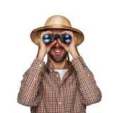 Mens die verrekijkers met reizigershoed kijken die over witte bac wordt geïsoleerd stock foto