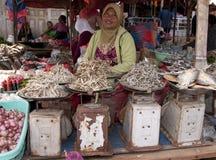Mens die vers fruitgroenten en fisch markt Indonesië verkopen Royalty-vrije Stock Foto's