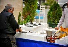 Mens die verse vissen op straatmarkt verkopen in Istanboel Stock Afbeeldingen