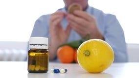 Mens die verse vruchten zoals alternatief analyseren aan vitaminenbehandeling met geneeskundepillen stock footage