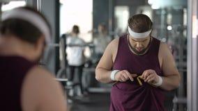 Mens die vette taille, ontevreden met zijn resultaat na het op dieet zijn en opleiding meten stock video