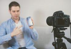 Mens die videoblog over mobiele telefoons maken stock foto's