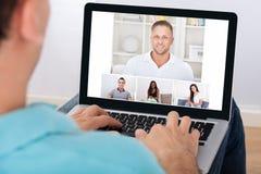Mens die videoconferentie met vrienden hebben Stock Afbeeldingen