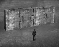 Mens die vier reusachtige concrete samen verbonden raadsels onder ogen zien Royalty-vrije Stock Afbeeldingen
