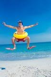 Mens die vinnen en rubberring dragen bij het strand stock foto's