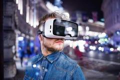 Mens die virtuele werkelijkheidsbeschermende brillen dragen De stad van de nacht Stock Foto