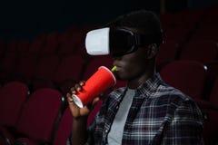 Mens die virtuele werkelijkheidshoofdtelefoon met behulp van terwijl het letten van op film stock afbeeldingen