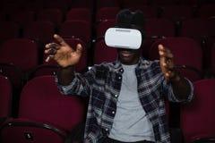 Mens die virtuele werkelijkheidshoofdtelefoon met behulp van terwijl het letten van op film royalty-vrije stock afbeelding
