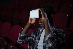 Mens die virtuele werkelijkheidshoofdtelefoon met behulp van terwijl het letten van op film stock foto