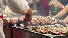 Mens die vleespennen bij de barbecuegrill roosteren bij een openluchtfestival stock footage