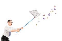 Mens die vlinders met netto vangen stock foto's