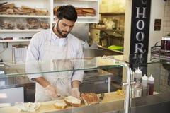 Mens die voedsel achter de teller voorbereiden bij een sandwichbar stock foto's