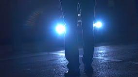 Mens die voor autokoplampen lopen stock footage
