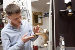 Mens die voor badkamersmateriaal winkelen in opslag Royalty-vrije Stock Afbeelding