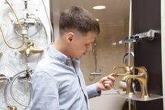 Mens die voor badkamersmateriaal winkelen in opslag Stock Foto's