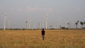 Mens die voor een windmolenbedrijf werken in het windlandbouwbedrijf die naar de windmolens lopen voor inspectie 4K stock videobeelden