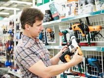 Mens die voor perforator in ijzerhandel winkelen Stock Foto's