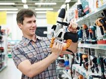 Mens die voor perforator in ijzerhandel winkelen Royalty-vrije Stock Foto's